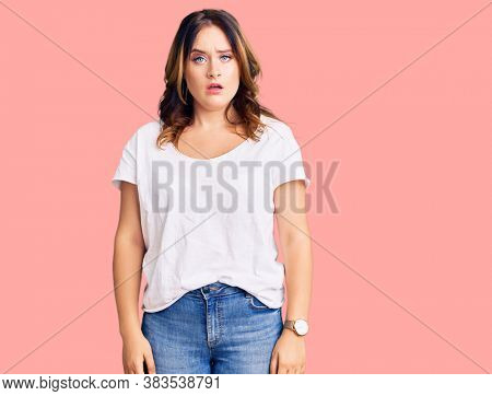Young beautiful caucasian woman wearing casual white tshirt in shock face, looking skeptical and sarcastic, surprised with open mouth