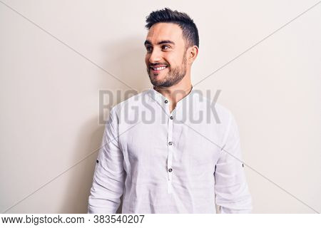 Young handsome man with beard wearing casual t-shirt standing over white background looking to side, relax profile pose with natural face and confident smile.