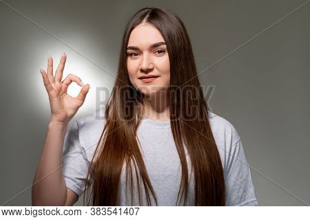 Satisfied Overweight Woman. Ok Sign. Confident Plus Size Lady In Gray T-shirt Showing Approving Gest