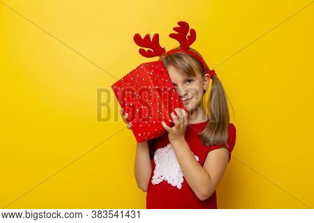 Beautiful Little Girl Wearing Deer Antlers Costume, Holding A Christmas Gift Isolated On Yellow Colo