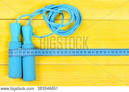 Sports Equipment In Cyan Color. Measuring Tape And Jump Rope