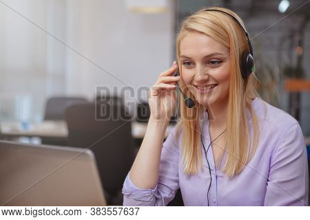 Beautiful Cheerful Woman Smiling Joyfully, Answering Customer Calls At The Call Center, Typing On He