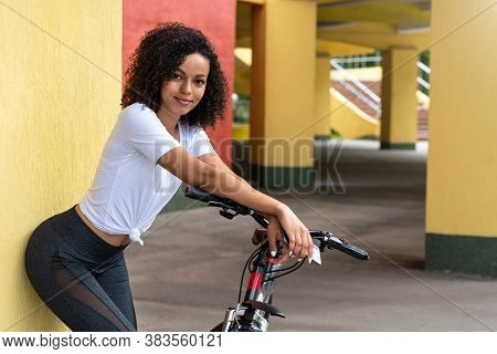 Happy, Young, Slender African-american Woman In Sportswear With A Bicycle On The Street In The City.