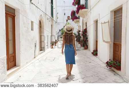 Back View Of Young Tourist Woman On Ancient Street In Old Town. Travel Woman In Straw Hat And Blue D