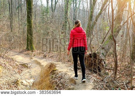 Young Woman Walking Away Alone On A Forest Path Wearing A Red Down Jacket In Autumn Winter