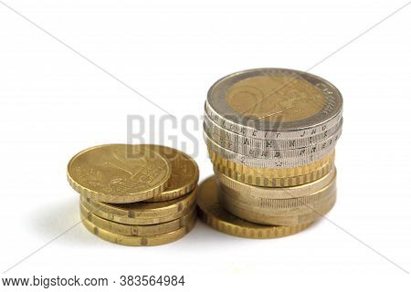 Stacks Of Euro Coins Of Different Denominations On A White Background Close-up Isolate. Money And Ex