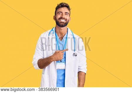 Young hispanic man wearing doctor uniform and stethoscope cheerful with a smile of face pointing with hand and finger up to the side with happy and natural expression on face