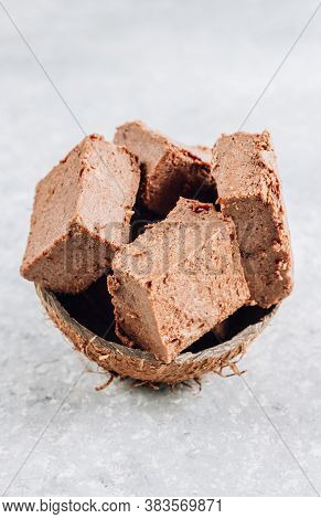 Raw Vegan Chocolate Fudge In A Coconut Shell On A Gray Background. 3 Ingredient - Coconut Oil, Banan