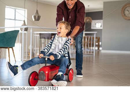 Senior man helping boy ride his toy car at home. Grandfather pushing kid car with little grandson inside to go faster. Excited boy and palyful elderly man playing together at home, copy space.