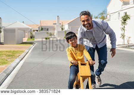 Happy latin father helping smiling boy to ride wooden balance cycle on street. Happy middle eastern child and young dad riding bike. Smiling daddy teaching son to ride a balance bicycle, copy space.