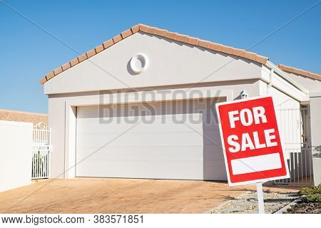 For sale sign outside a family house. Sale signboard outside home in lawn. Real estate board in front of new house for sale with copy space.