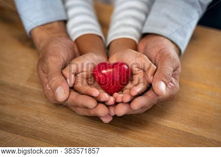 Family holding red heart in hands on wooden background. Top view of father and daughter hands protect heart. High angle view of man and little girl hands holding red heart: adoption foster family.