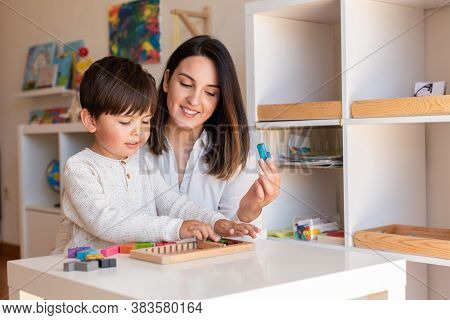 Lillte Kid Playing With A Tetris Wood Puzzle And Mother Or Teacher Help. Homeshooling. Learning Comm