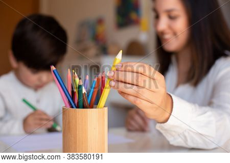 Little Preschooler Kid Drawing With Coloured Pencils With Mother Or Teacher Educator. Focus On The P