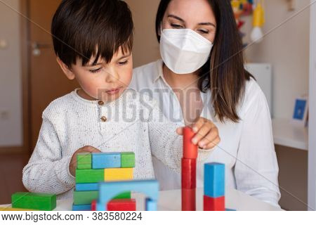 Liltle Preschooler Kid Playing With Wood Blocks And Teacher Educador Help Using Face Mask For Corona