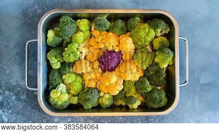 Different colourful cauliflower florets in baking dish before cooking Cabbage gratin. Concept healthy eating.