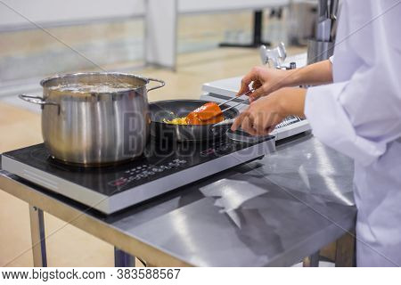 Chef Cooking Cereal, Grain In Frying Pan With Oil On Electric Stove At Cuisine Of Restaurant. Profes