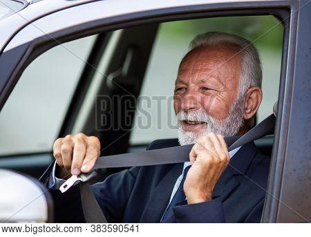 Senior Man Sitting In Car And Tying A Seatbelt