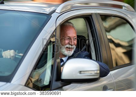 Portrait Of Happy Senior Man In Business Suit Driving Car With Elbow On Window