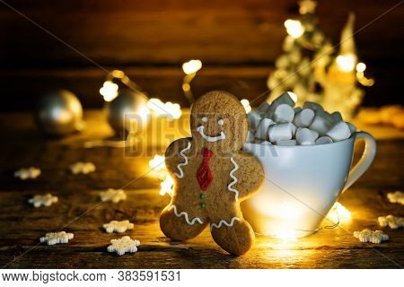 Christmas Holidays Wood Background With Cup Of Cocoa With Marshmallow, Luminous Garland And Cookie