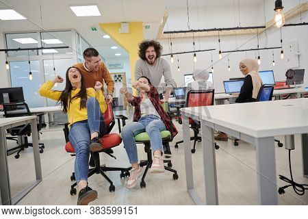 business people having fun while racing on office chairs