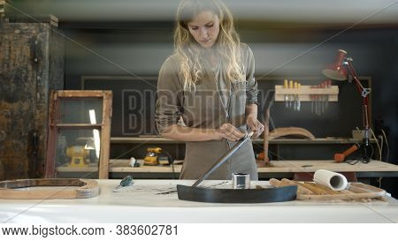 Young Woman Restorer, Polishing A Black Wooden Detail In Workshop. A Woman In Worksuit Working At Th