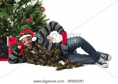 Happy African American Man Lying Beside A Christmas Tree
