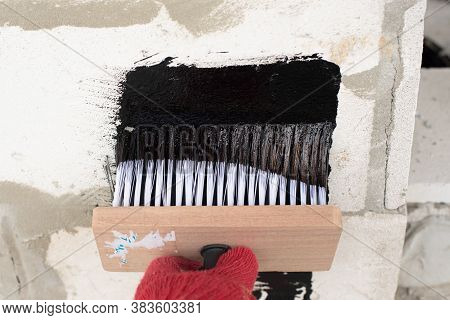 Roofers Hand In Red Mittens Holding A Brush