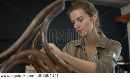 A Working Female Carpenter Peels Off Paint From Rocking Chair Legs With A Spatula, Restorer In A Wor