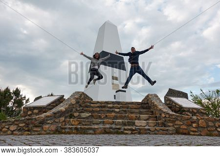 Vila De Rei, Portugal - March 30, 2019: Couple Jumping Typical Tourist Photo In Geographical Center