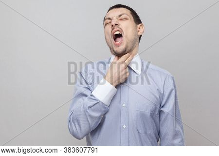 Throat Pain. Portrait Of Unhappy Handsome Bristle Businessman In Classic Light Blue Shirt Standing,