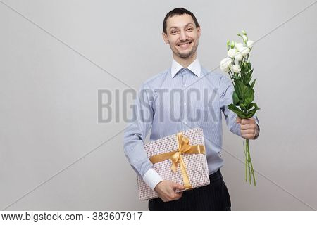 Presents For Birthday. Charming Pleasure Romantic Young Man In Blue Shirt Holding Bouquet Of White F
