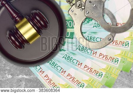 200 Russian Rubles Bills And Judge Hammer With Police Handcuffs On Court Desk. Concept Of Judicial T