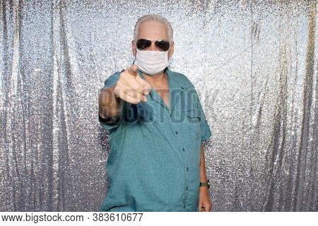 Photo Booth. A  Caucasian Man wears a Anti-Covid 19 Face Mask as he points his finger at you the viewer as he poses for photos in a Photo Booth with a silver sequin background.