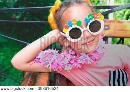 Beautiful Caucasian Girl Wearing Happy Birthday Sunglasses And Hawaiian Lei Garland. Happy Girl Sele