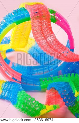 Curved Path. Fragment Of Kids Plastic Colorful Railway On Pink Background Resembling Path, Track, Ro