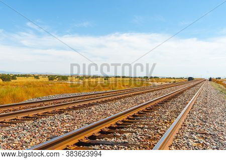 Diminishing Perspective Of Railway Tracks Disappearing To Horizon  Through Flat Plains Of New Mexico