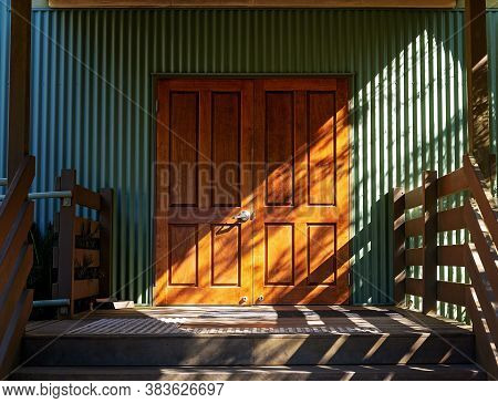 Entrance Door To A Building With The Sun Slanting In At An Angle