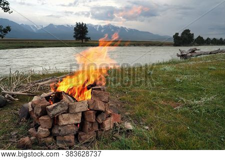 Summer Landscape With A Bonfire With A Large Bright Flame Against The Background Of High Snow-capped