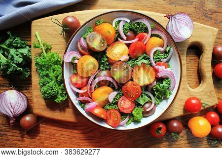 Fresh Green Salad With Cherry Tomatoes, Cabbage Kale, Onions On Cutting Board. Wooden Background