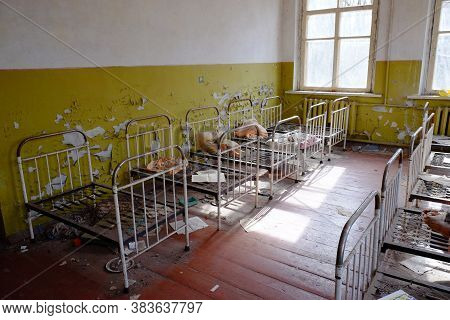 Old Children's Beds In An Abandoned Kindergarten. The Interior Of A Room In One Of The Buildings In