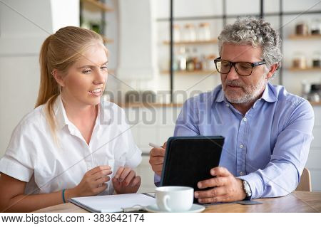 Focused Friendly Mature Male Mentor Explaining Work Details To Intern. Business Man Showing Tablet S