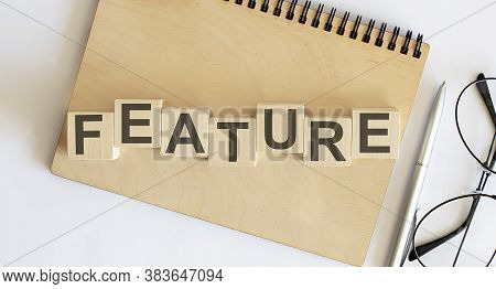 Feature Word Made With Building Blocks On Wooden Notepad
