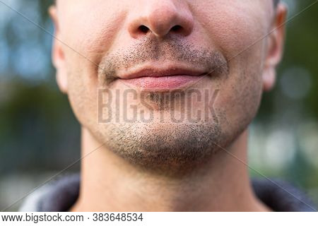 Beautiful Male Lips Of Caucasian Appearance Close-up. The Slight Smile And The Bristle Of Stubble On