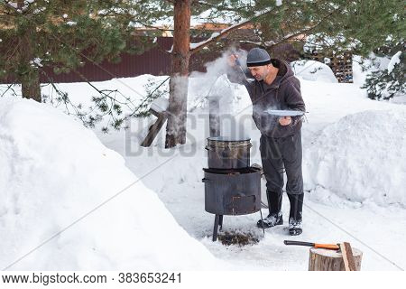 Caucasian Man Prepares Food On A Fire In Winter Outdoors Near Snowdrifts And Pines, Tastes Soup From