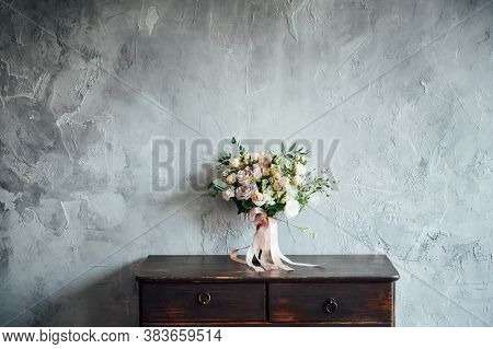 Wedding Bouquet On Dresser Near Gray Wall With Vintage Texture