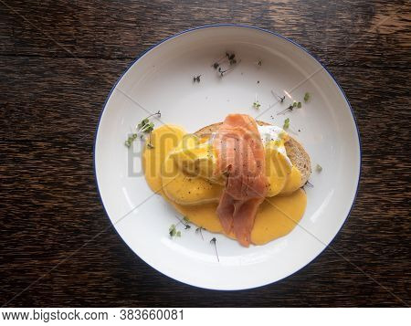 Smoked Salmon Eggs Benedict Close Up On White Plate, Lox Salmon, Chives, Hollandaise Sauce, Poached