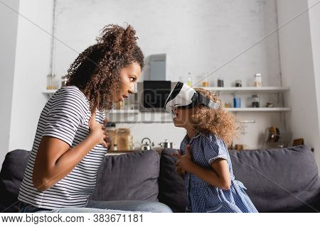 Excited African American Babysitter And Kid In Vr Headset Looking At Each Other While Holding Hands