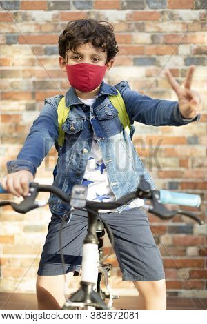 A Little Boy On A Bicycle. He Is On The Street And Wearing A Face Mask As A Precaution For The Covid