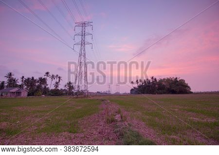 Atmospheric Refraction Sunset Of Electric Tower In The Paddy Field.